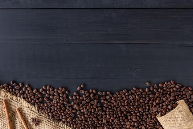 Granos de café en saco de la arpillera en viejo fondo de madera. vista superior