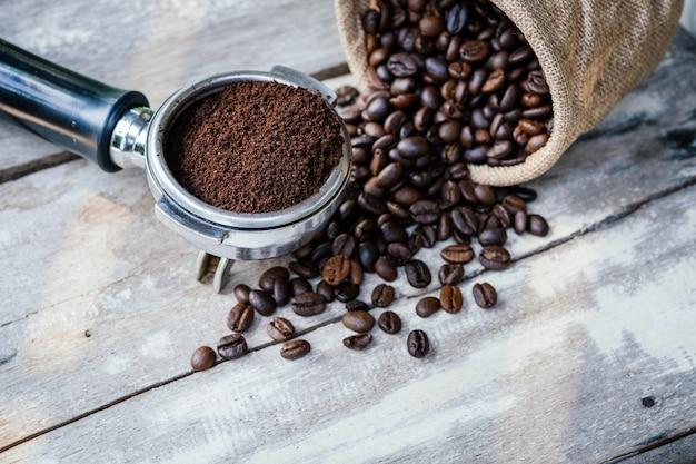 Granos de café en saco y portafiltros en mesa de madera blanca vieja