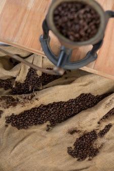 Granos de café en saco textil con molinillo de café