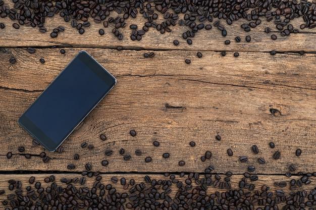 Granos de café de smartphone en la vista superior del escritorio
