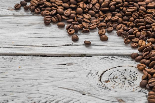 Granos de café sobre fondo blanco de madera, primer plano