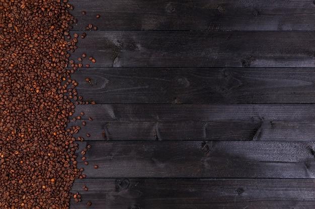Granos de café sobre fondo de madera oscura.
