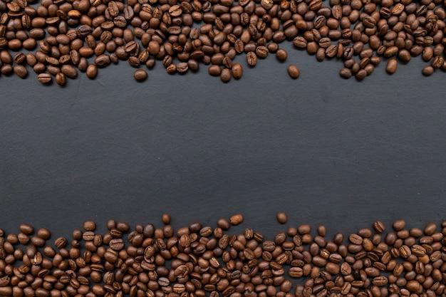 Granos de café sobre fondo de mesa negro antiguo