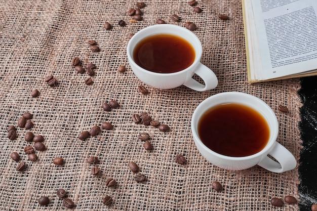 Granos de café sobre fondo negro con bebida en arpillera.