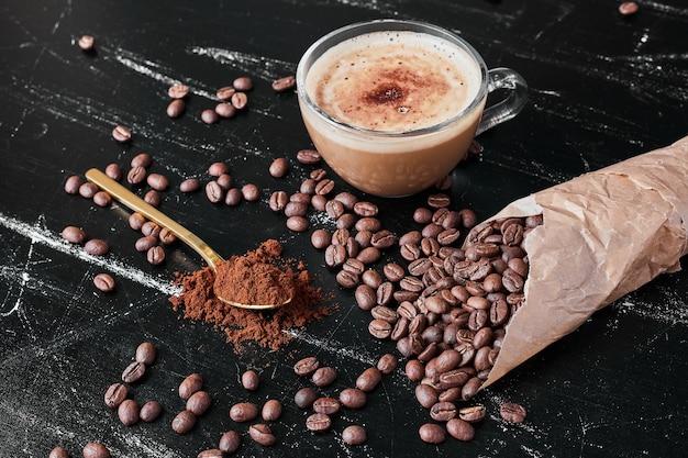 Granos de café sobre fondo negro con una taza de bebida.
