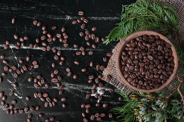 Granos de café sobre fondo negro en la taza de madera.