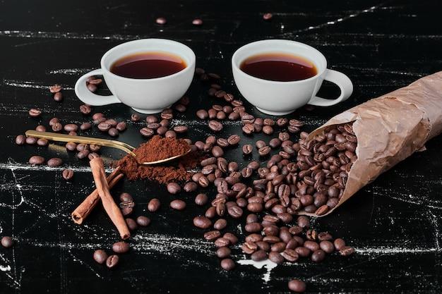 Granos de café sobre fondo negro con tazas de bebida.