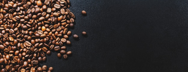 Granos de café sobre fondo oscuro. vista superior. concepto de café. bandera. Foto Premium