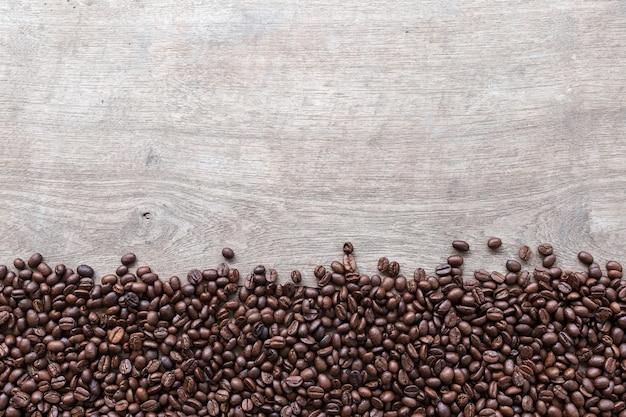 Granos de café sobre fondo de piso de madera. vista superior