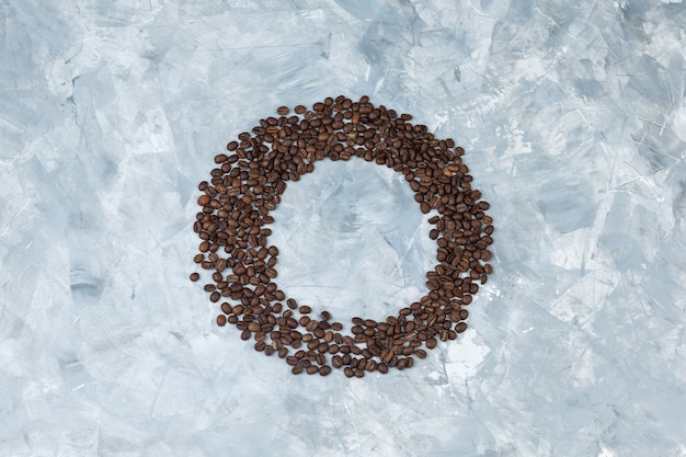Granos de café sobre un fondo de yeso gris. endecha plana.
