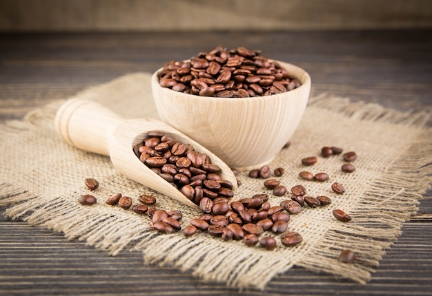 Granos de café sobre un mantel de mesa de madera