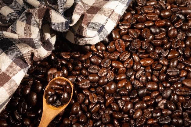 Granos de café sobre tela de lino marrón.