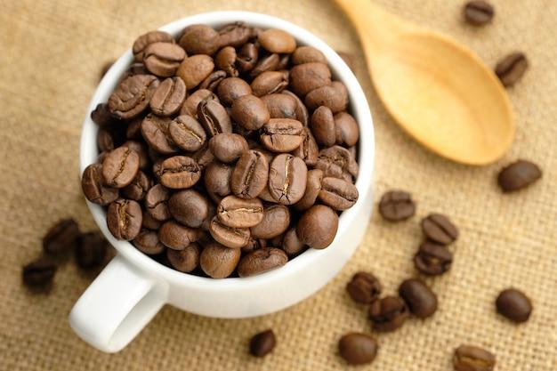Granos de café en la taza blanca colocada sobre tela de saco.