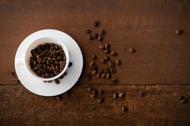 Los granos de café en la taza blanca están en la mesa de madera de color marrón oscuro, con fondo borroso.