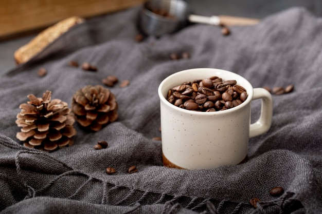 Granos de café en una taza blanca sobre una bufanda gris