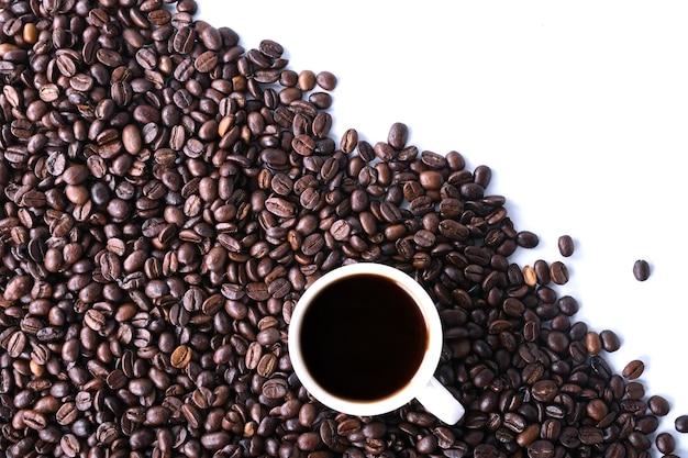Granos de café y una taza de café aislado sobre un fondo blanco.