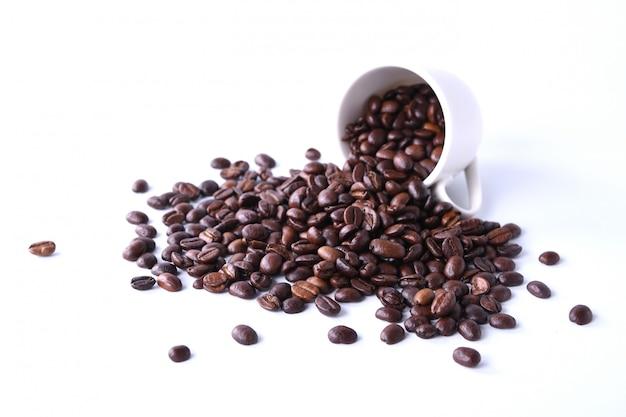 Granos de café y taza de café aislado