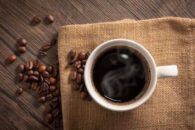 Granos de café y una taza de café blanco en bolsa de saco sobre fondo de madera