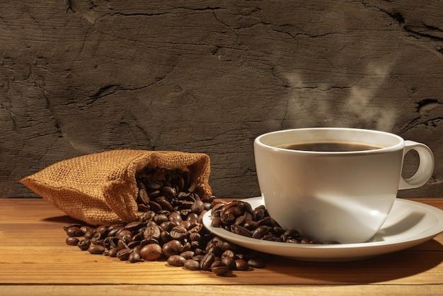 Granos de café y una taza de café caliente en la pared marrón
