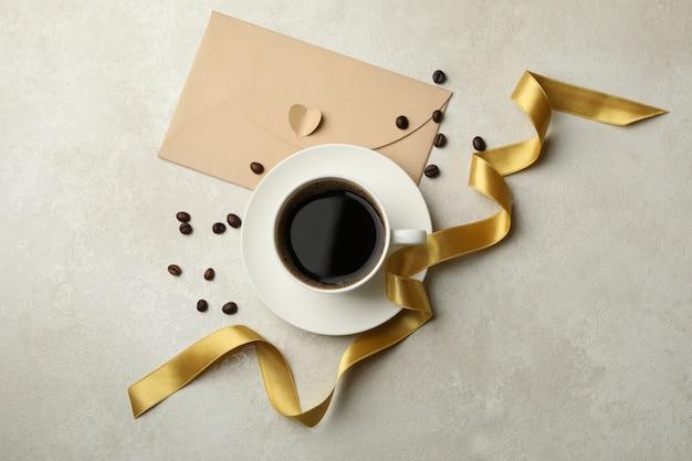 Granos de café, taza de café, cinta y sobre sobre fondo de textura