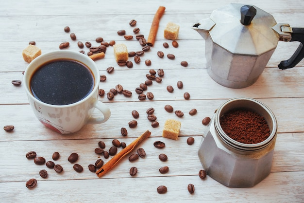 Granos de café y una taza de café en la mesa en