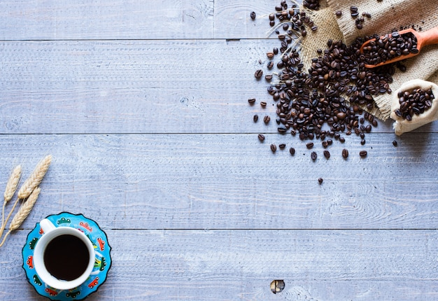 Granos de café y taza de café con otros componentes sobre fondo de madera diferente. espacio libre para texto