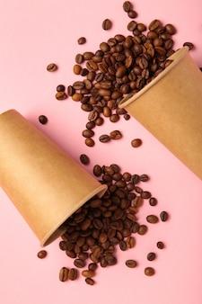 Granos de café y taza de café de papel sobre fondo rosa. vista superior.