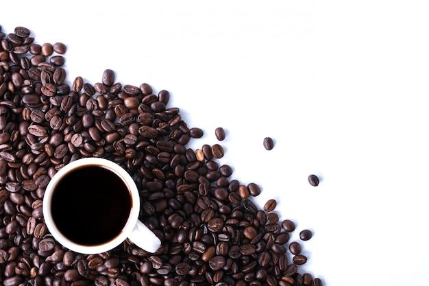 Granos de café y taza con copyspace blanco