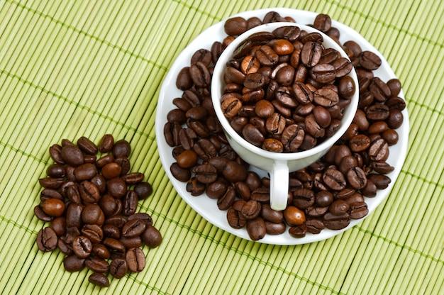Granos de café en una taza - foco en el primer plano -