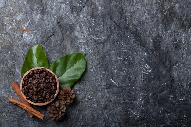 Granos de café en taza de madera en hoja verde, pino en piedra negra