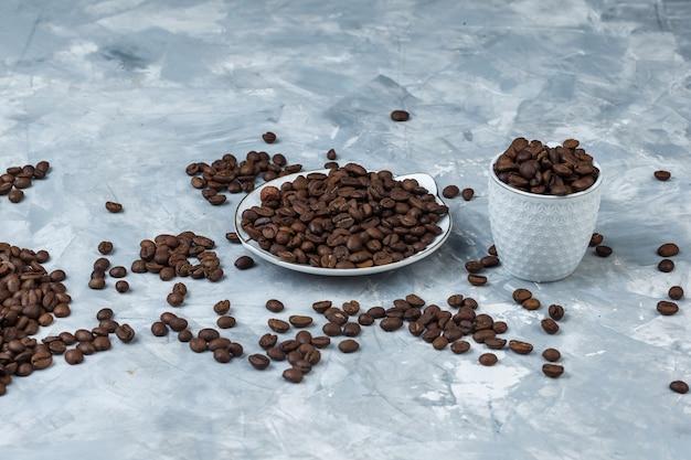 Granos de café en taza y plato blanco sobre un fondo de yeso gris. vista de ángulo alto.