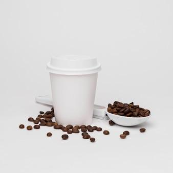 Granos de café y taza sobre fondo blanco.