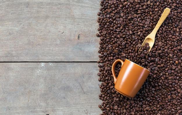 Granos de café y taza sobre fondo de piso de madera. vista superior