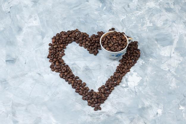 Granos de café en una taza sobre un fondo de yeso gris. vista de ángulo alto.