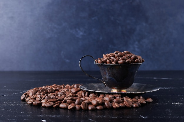 Granos de café en una taza y sobre el negro