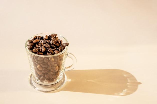 Granos de café en una taza de vidrio sobre un fondo claro