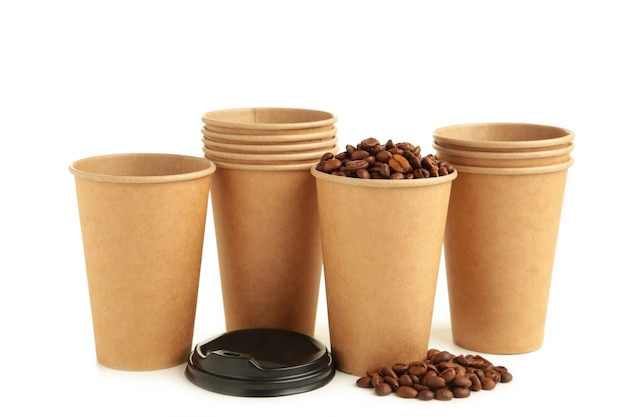 Granos de café y tazas de café de papel aisladas sobre fondo blanco. vista superior.