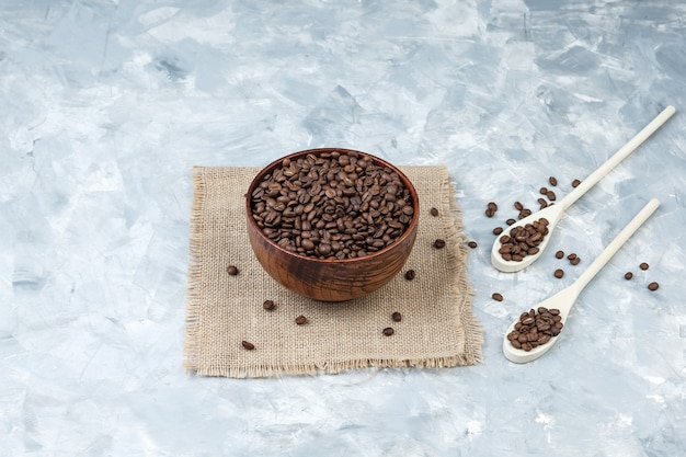 Granos de café en un tazón y cucharas de madera sobre yeso y un pedazo de fondo de saco. vista de ángulo alto.