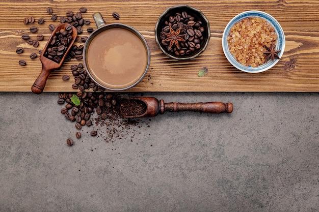 Granos de café tostados con configuración de taza de café en piedra oscura.
