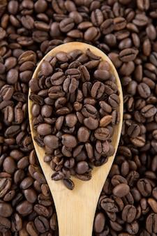 Granos de café tostados con cuchara de madera