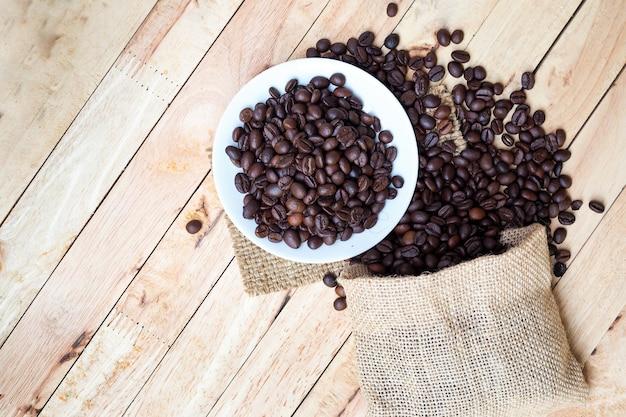 Los granos de café tostados se derraman de un saco en el fondo de la mesa de madera. vista superior