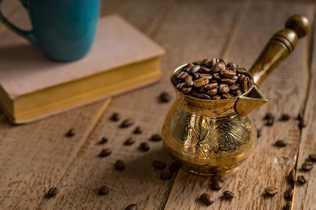 Los granos de café tostados frescos en cezve cerraron el libro y la taza en la tabla de madera.