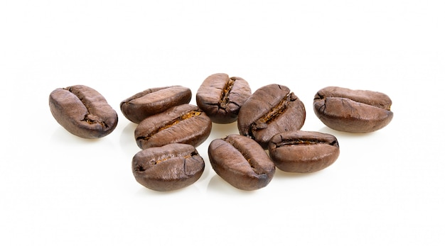 Granos de café tostados en mesa blanca.