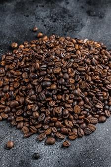 Granos de café tostados en mesa rústica.