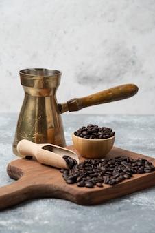 Granos de café tostados oscuros y cafetera sobre tabla de cortar de madera.