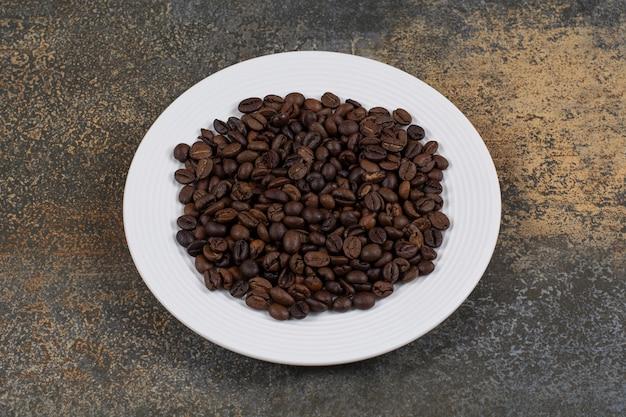 Granos de café tostados en un plato blanco.