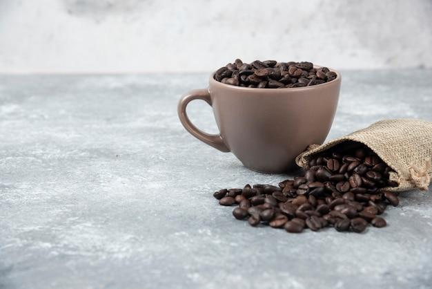 Granos de café tostados en saco de arpillera y en taza sobre mármol.