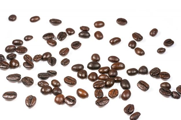 Los granos de café tostados salpican aislado en un fondo blanco.