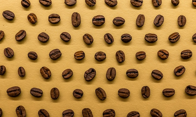 Granos de café tostados sobre fondo dorado brillante, se pueden utilizar como fondo de pantalla