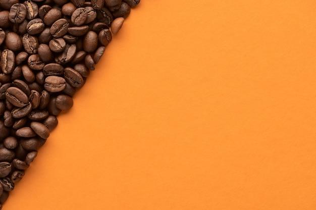 Granos de café tostados sobre fondo naranja con espacio de copia. cerrar vista superior. foto de alta calidad